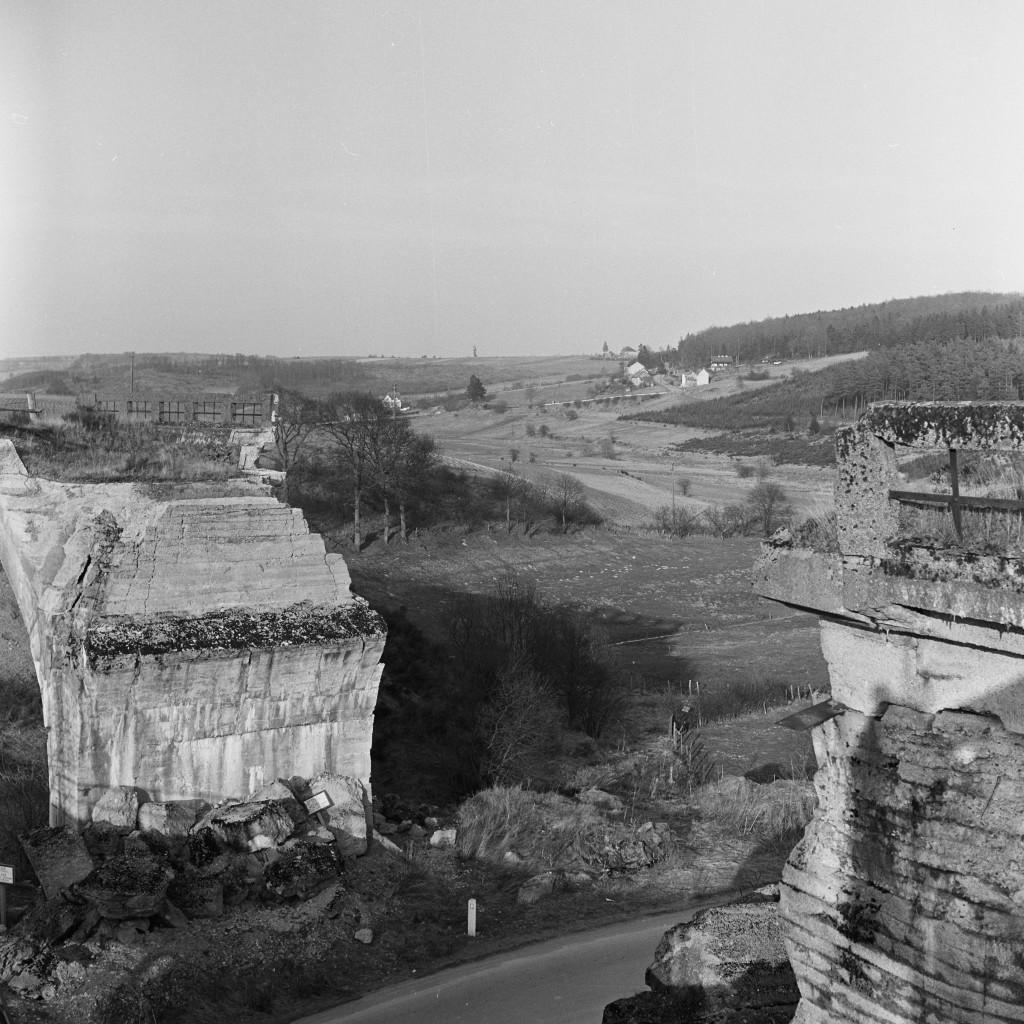 Un pont de la ligne de la Vennbahn détruit pendant la Seconde Guerre mondiale, près de Saint-Vith. Dans l'après-guerre, les politiciens ont rechigné à payer les frais considérables nécessaires pour reconstruire tous les viaducs sur l'ensemble de  la ligne de la Vennbahn. Pour cette raison, seulement quelques tronçons de la Vennbahn ont été exploités. En 1961, à partir de Luxembourg, les trains ne circulaient plus qu'entre Wilwerdange et Burg-Reuland en Belgique. (Photo Paul Aschman 1961, © Photothèque Ville de Luxembourg)